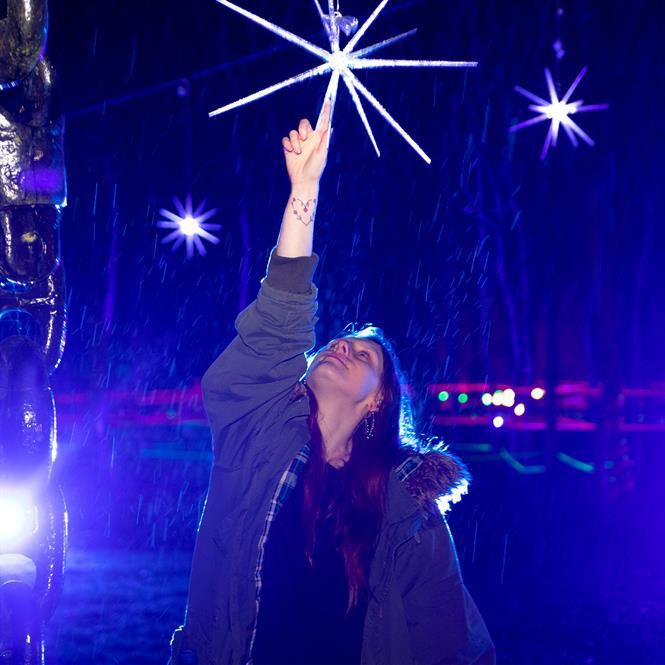 Person interacting with installation at Illuminated Arboretum in 2020