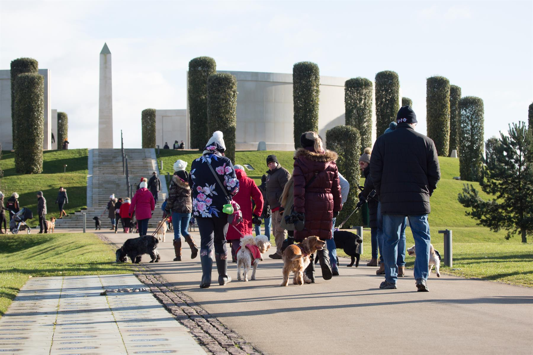 A number of dogs and their owners walk toward the Armed Forces Memorial at a Paws for Remembrance Event.
