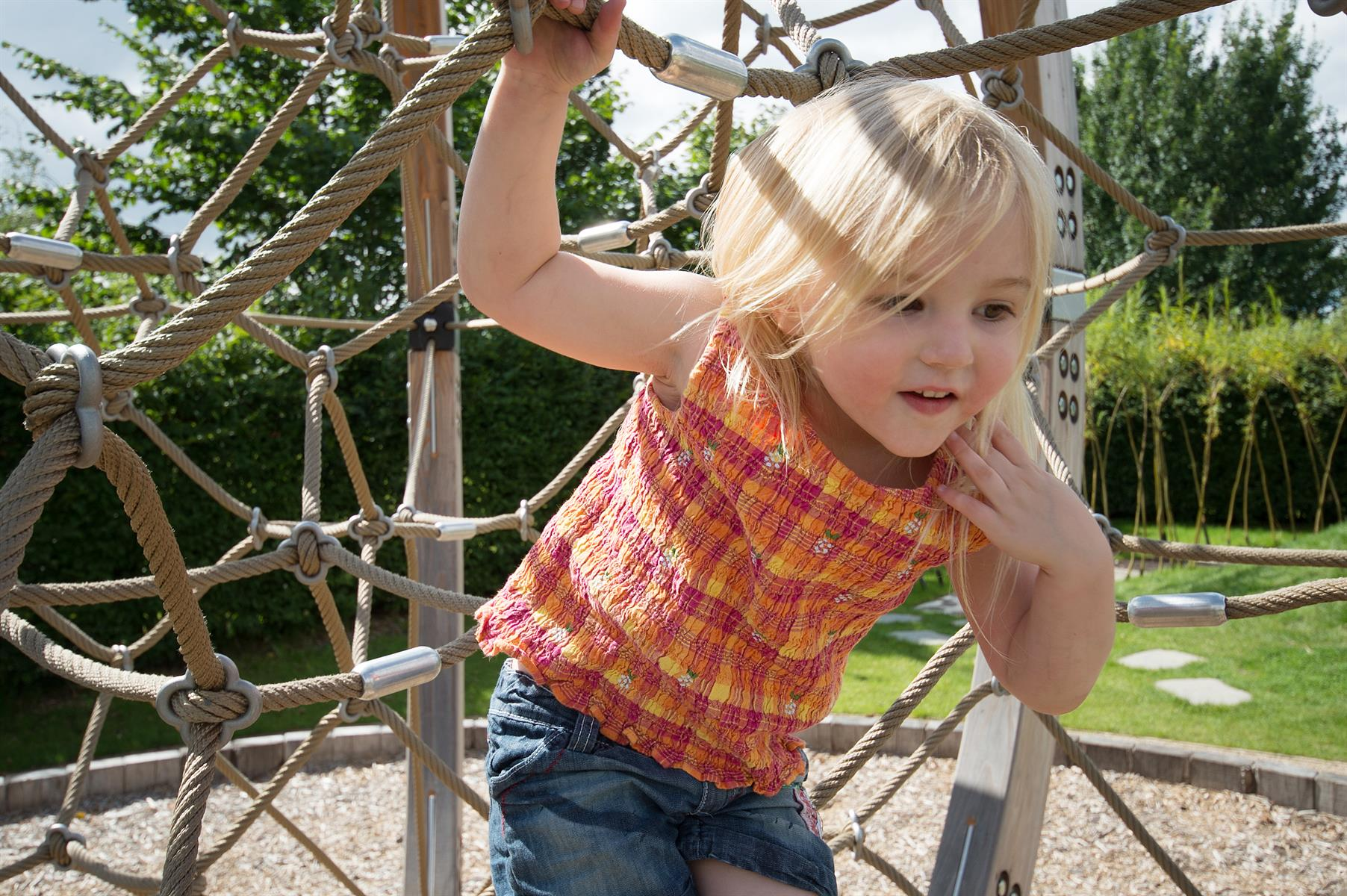 Young girl plays in sensory play frame at the Arboretum