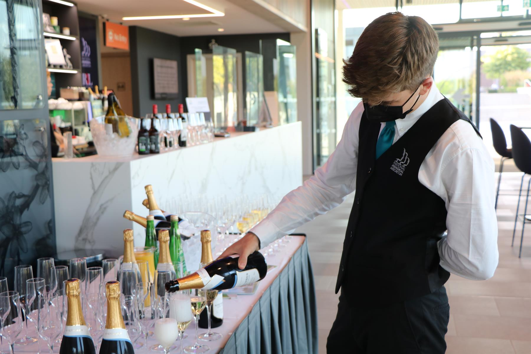 Foodservices Assistant pouring champagne at event